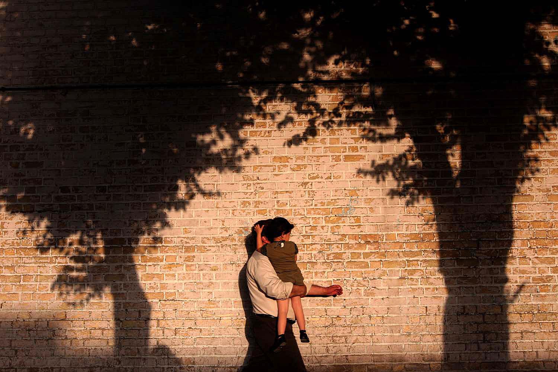 Seorang bapak menggendong anaknya di Imam Khomeini Street, Yazd.