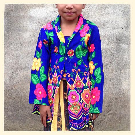 Bocah perempuan di daerah Sembalun yang terletak di kaki Gunung Rinjani, Lombok, Nusa Tenggara Barat, mengenakan baju bermotif warna-warni saat menghadiri upacara adat Mengayu Ayu.