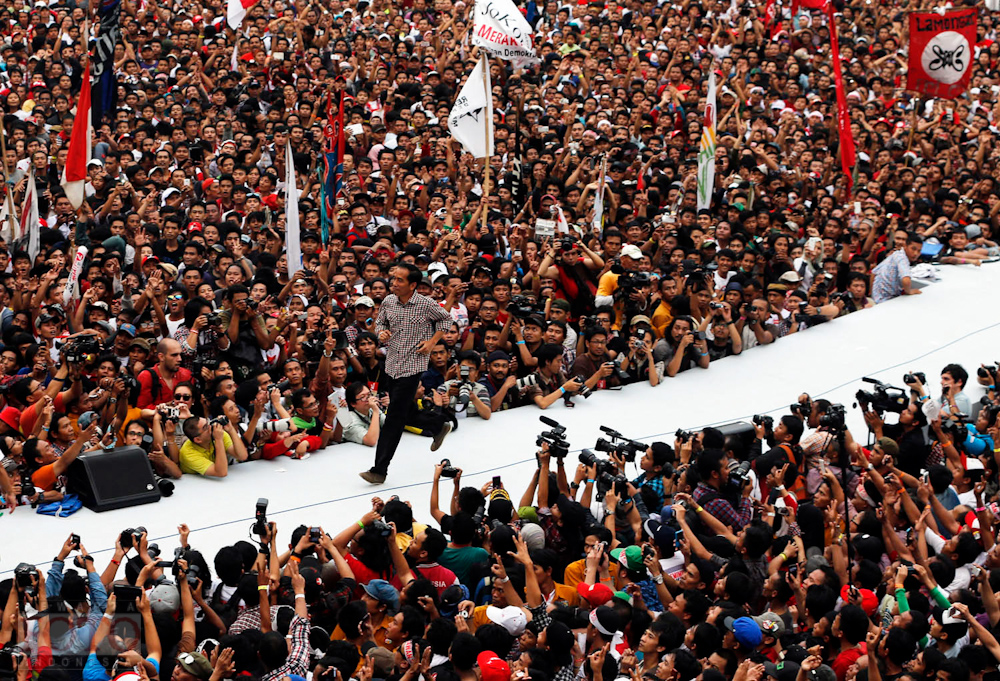 "Indonesian presidential candidate Joko ""Jokowi"" Widodo runs on the stage after delivering a speech in front of his supporters at Gelora Bung Karno stadium in Jakarta"
