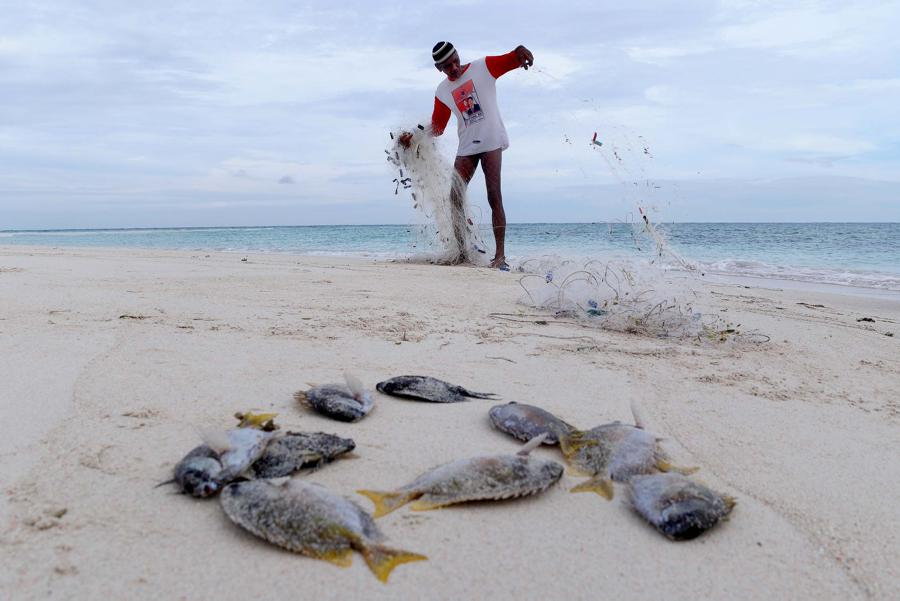 Bohe (70 tahun) , seorang suku bajau , merapikan jaring seusai menangkap ikan di gosong Kabak Tengah, Pulau Derawan